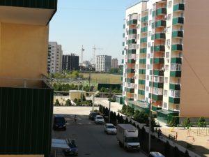 Вид с балкона, в близи детская площадка, а в дали спортивная.